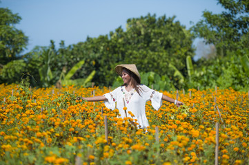 happy and beautiful young Asian woman wearing traditional hat enjoying excited the fresh beauty of orange marigold flowers field natural landscape
