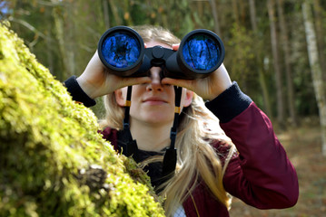 Caucasian girl is looking through the binoculars in the forest.