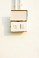 Electric switch on the white wall.