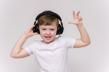 cute 6 year old boy listening to music on headphones on a white background in different poses