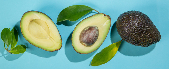 Slices of avocado on bright background. Whole and half with leaves. Design element for product label