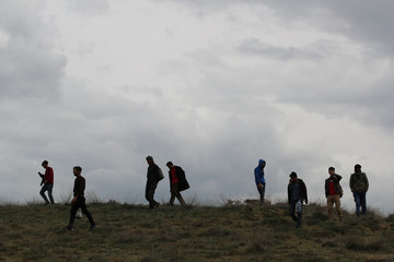 Group of Afghan migrants walk along a path on mountains after crossing the Turkey-Iran border near Erzurum