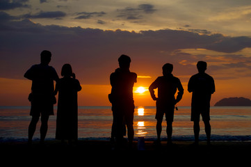 silhouette people watching sunset