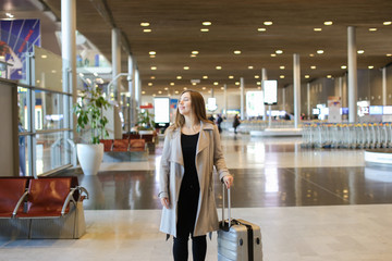 European woman wearing grey coat walking in airport hall with valise. Concept of traveling abroad and happy passenger.