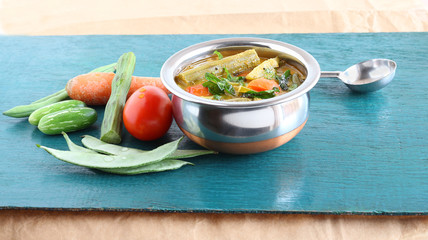 Drumstick sambar, a semi-liquid south Indian vegetarian food made from this vegetable and others like tomato, carrot, ivy gourd and onion and lentils, in a steel bowl.
