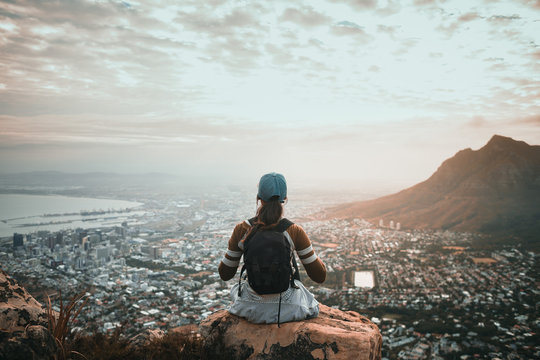 Young woman sitting on top of mountain overlooking city