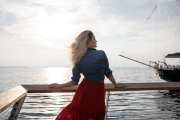Beautiful woman in red dress on the background of the sea.