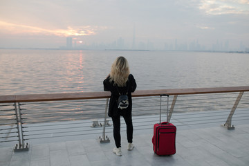 Rear view of a woman taking a photo of the city from the ocean side.