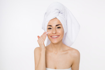 Face cream. Skin care. Beautiful smiling woman with a towel on her head after showering. Cosmetology. Beauty & Spa