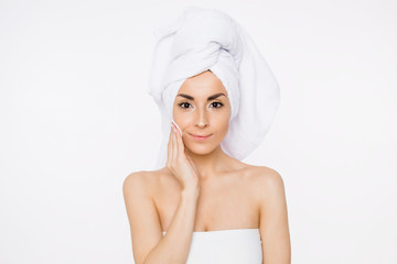 Removing makeup. Beauty and spa. A beautiful smiling woman with a towel on her head moisturizes or cleanses her face from makeup using cotton pads. Cosmetology. Women Health