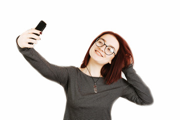 Cheerful red hair young woman with eye glasses taking selfie with smartphone isolated on white