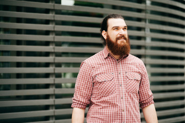 Portrait of bearded hipster man in red shirt outside and looking away