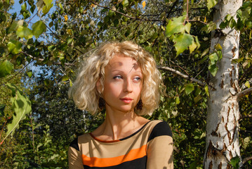 A portrait of a pretty young woman with a curly, blond hair and blue eyes, standing in a green park near a birch and looking into the distance. The photo was shot in the park, Kiev, Ukraine.