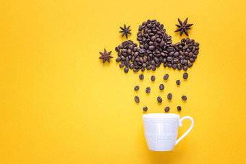 Coffee beans in shape of rainy cloud with anise stars and white cup on yellowbackground.