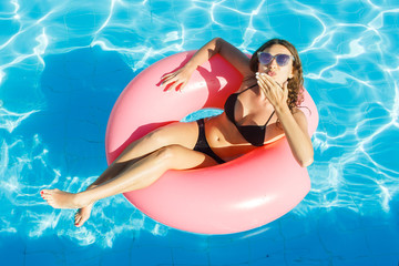 bikini girl with sunglasses relaxed on pink inflatable pool ring