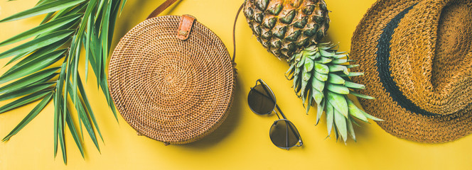 Colorful summer female fashion outfit flat-lay. Straw hat, bamboo bag, sunglasses, palm branches, pineapple over yellow background, top view, wide composition. Summer fashion, holiday concept