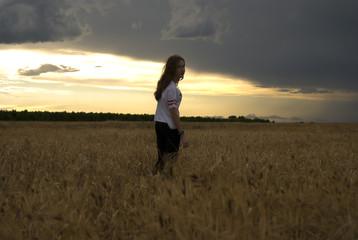chica joven, mujer, posando en medio de un campo de trigo al atardecer