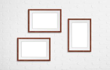 Three photo frames on white bricks background, interior decor mockup