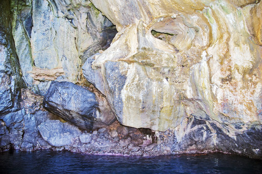 A natural grotto where the cobalt blue seawater contrast with the reddish encrustation  on the submerged rock due to the zinc oxide