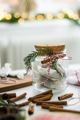 Decorated glass jar with christmas candy and cinnamon decorations