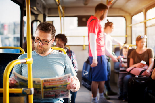 Young man is focused on reading his newspapers while taking a bus ride.