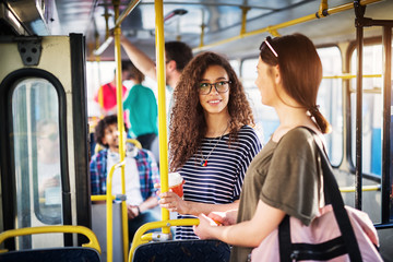 Two beautiful young women are drinking coffee and having a chat while standing in the bus and holding onto the bars.