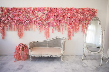 Old carved daybed with soft upholstery against a white wall decorated with pink flowers. Gorgeous garland. The interior decor is romantic, wedding photo zone. Imitation in the mirror. Full-length
