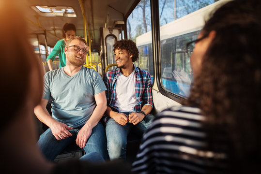 Two young handsome male friends are sitting together on a bus talking and having chuckles.