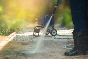 High pressure cleaning, side view.Man cleaning dirty walkway with high pressure water cleaner ,professional cleaning services concept..