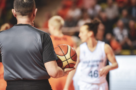 Referee holds the ball during women basketball match