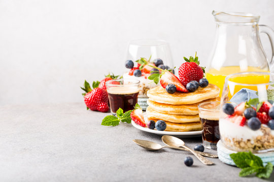 Breakfast background with fresh pancakes and berries on light gray concrete table. Healthy food concept with copy space.