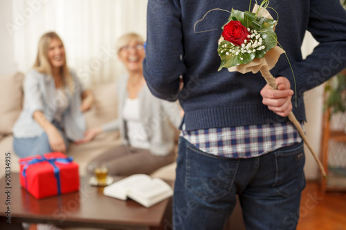 Young man holding flowers bouquet behind the back for his mother. Mother and daughter talking. Mother's day. Happy family moments at home