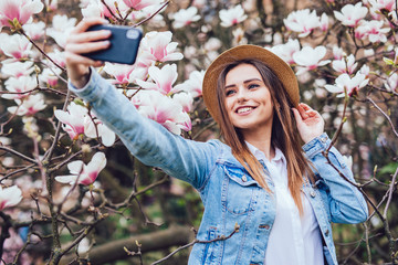 Spring portrait of sensual beauty woman in straw hat at blossom garden park making selfie on phone against magnolia flowers