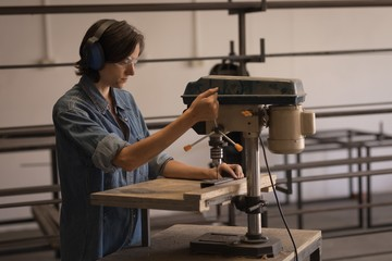Female welder using vertical drilling machine