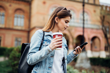 Pretty girl stand on the street typing on phone and drink coffee to go