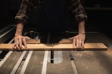 Female welder measuring a wooden piece in workshop