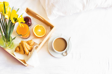 Morning breakfast in bed wooden tray with a cup of coffee croissant orange juice fresh orange jam bouquet of flowers daffodils. Top view Morning at Hotel Background Concept Interior Copy Space
