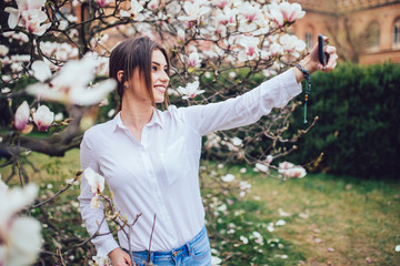 Beautiful caucasian woman making selfie in blossom magnolia garden.