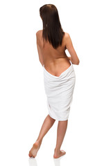 Sexy naked woman wrapped in white towel isolated on white background