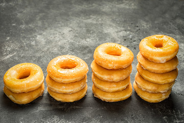 few piles of donuts stacked in a row with a growing trend. concept of business growth.