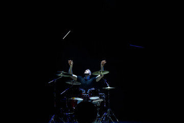 Drummer in a cap and headphones plays drums at a concert under white light in a smoke
