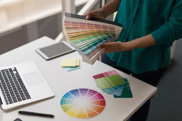 Female graphic designer holding color shade cards