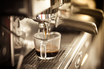 Professional coffee machine preparing cup of coffee.