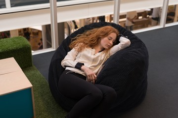 Businesswoman sleeping on bean bag in office lobby