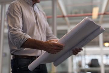 Male architect looking at blueprint in office