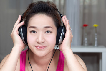 Young asian beautiful woman enjoy listening the music at home