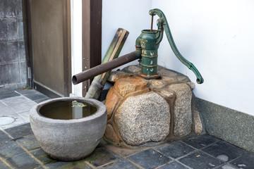 ancienne  pompe à eau et récipient en pierre a l'entrée d'une maison japonaise