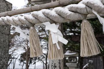 corde sacrée recouverte en partie de neige à l'entrée d'un temple shinto
