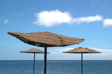 parasols with palm tree mesh at a beach of a canary island