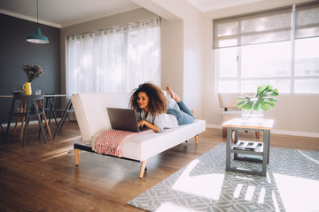 african happy woman lying on couch with laptop